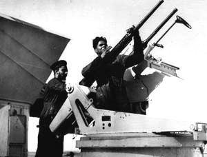 Two crew of HMIS Narbada cleaning a twin Oerlikon gun
